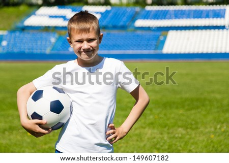 Boy with soccer ball at the stadium.