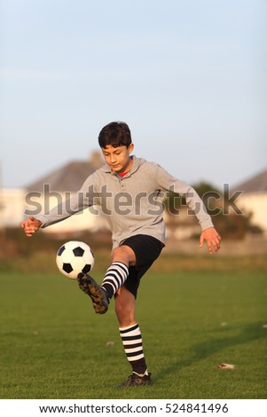Boy with soccer ball outside in the golden hour near sunset - warm tones