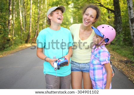 Boy with the car and remote control laughing with mother and younger sister in the green park - stock photo