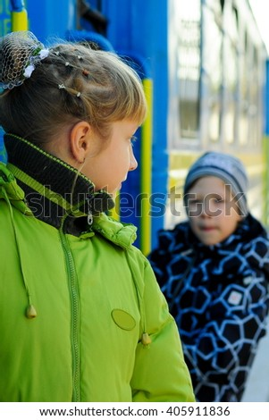 boy with the girl on the platform, holding on to the railing of blue wagon - stock photo