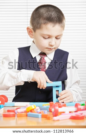 Boy with toy blocks standing at desk