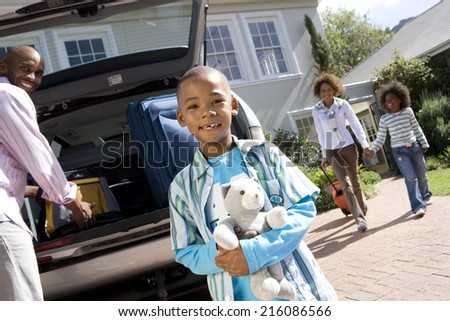 Boy (6-8) with toy by father loading back of car, portrait (tilt) - stock photo