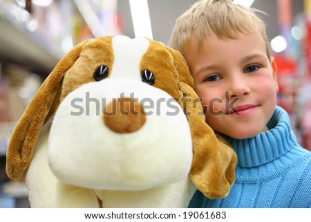 Boy with toy dog in shop - stock photo