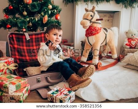 boy with toy horse near Christmas tree - stock photo