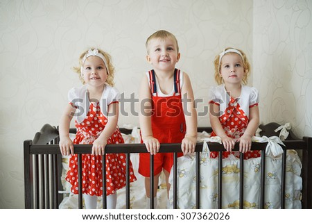 boy with two girls twins in cot - stock photo