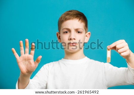 Boy with white adhesive plaster on his hand - stock photo