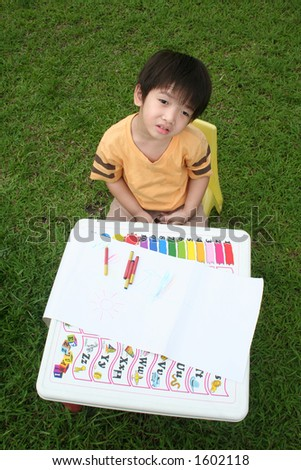 Boy with wondering expression at the drawing table - stock photo