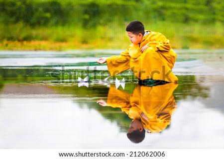 Boy with yellow raincoat splashing happily. - stock photo