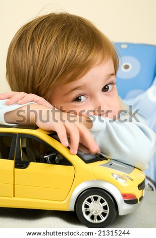 Boy with yellow toy car - stock photo