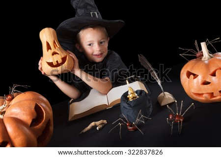 Boy wizard Halloween with pumpkins, magic book, spiders, dead man's fingers and candles, Isolated on black background - stock photo
