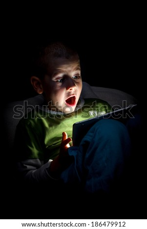 Boy wonder looking at the tablet - stock photo