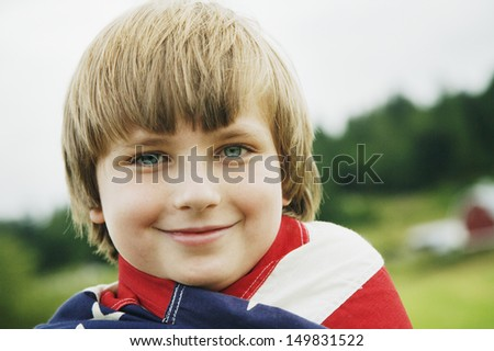 Boy wrapped in American flag - stock photo