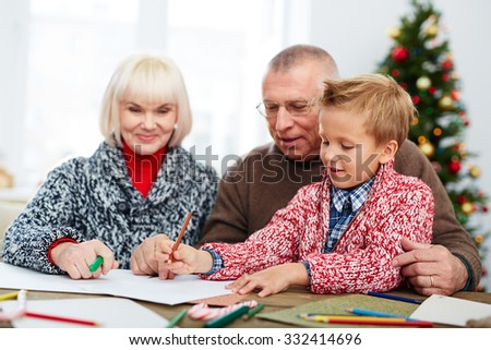 Boy writing a letter to Santa with his grandparents - stock photo