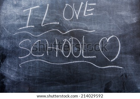 Boy writing I love on a blackboard. - stock photo