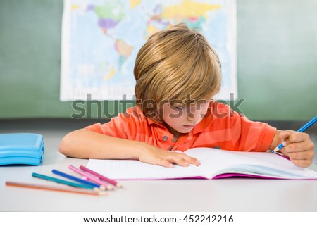 Boy writing on book in classroom at school