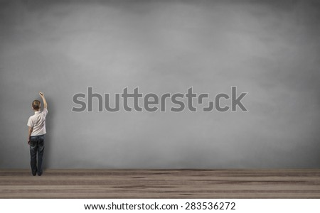 boy writing on the wall - stock photo