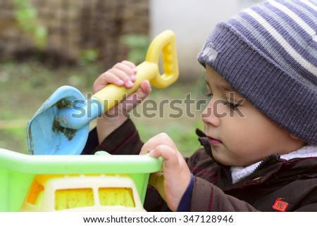 boy 2 years old playing with a machine outdoors - stock photo