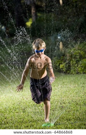 Boy, 9 years, wearing swim goggles and swimsuit getting soaked in lawn sprinkler - stock photo