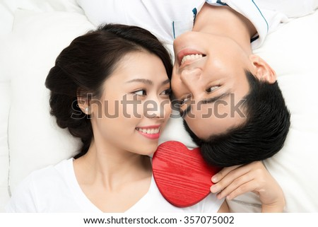 Boyfriend and girlfriend lying taking selfie with happy face expression looking each other in eyes. Couple of asian lovers at the beginning of love story having fun together.