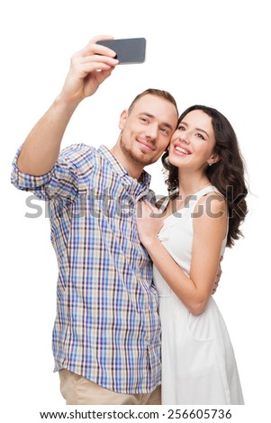 Boyfriend and girlfriend making photo on phone. They look happy. Isolated on white background - stock photo