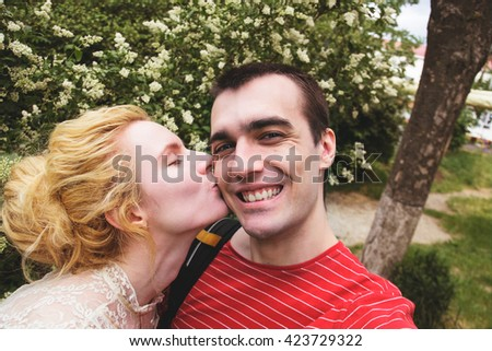 boyfriend girlfriend selfie on a walk. Young couple taking a selfie outdoors. Man holding a camera and taking a self portrait with woman kissing him. - stock photo