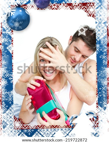 Boyfriend giving a surprise to her girlfriend against christmas themed frame - stock photo
