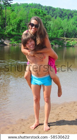 Boyfriend giving girlfriend piggy back ride at the river bank - stock photo