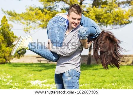 Boyfriend giving his girlfriend a piggyback ride - stock photo