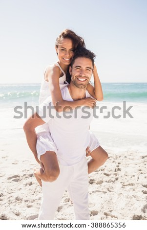 Boyfriend giving piggy back to girlfriend at the beach