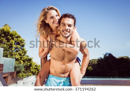 Boyfriend giving piggy back to his girlfriend by the pool - stock photo