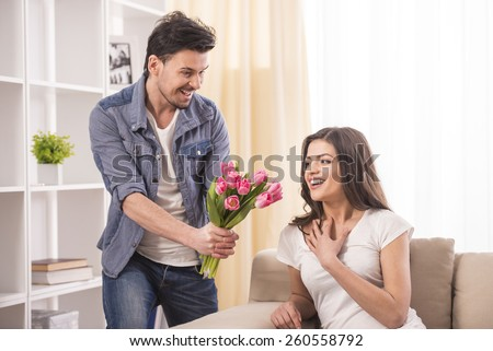 Boyfriend is giving flowers to his beautiful girlfriend at home. - stock photo