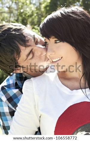 Boyfriend kissing his girlfriend on the cheek - stock photo