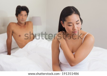 Boyfriend looking at girlfriend sitting on end of bed at home in bedroom