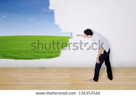 Boyfriend painting green field on wall - stock photo