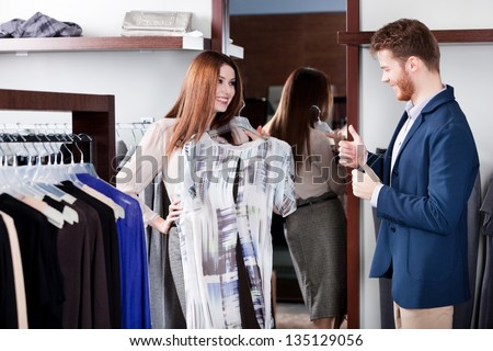 Boyfriend thumbs up when his girlfriend tries the dress on - stock photo