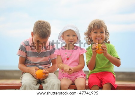 boys and girl with oranges and one little girl with panama hat is sitting on wooden bench. boy wearing stripped t-shirt looking at orange. focus on face of girl with orange. - stock photo
