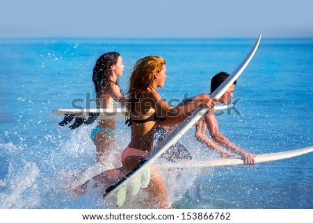 Boys and girls teen surfers running jumping on surfboards at the beach - stock photo
