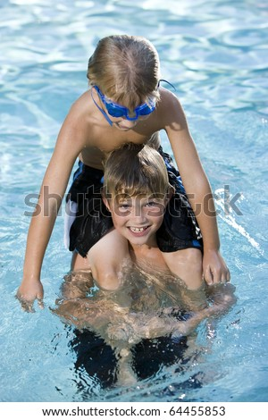 Boys, 7 and 9 years, playing in swimming pool, sitting on shoulders - stock photo