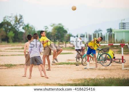 boys are playing football in the sunshine day. - stock photo