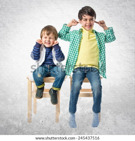 Boys covering his ears over textured background.  - stock photo