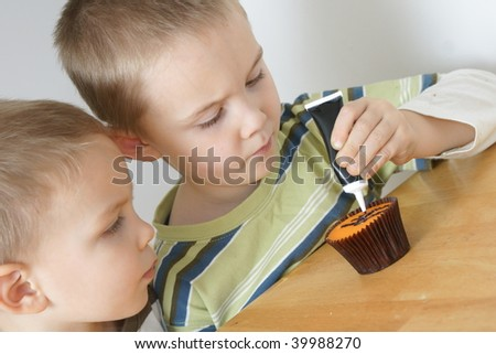 boys decorating a cup-cake - stock photo