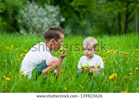 boys eat apple on a grass outdoors in spring park - stock photo