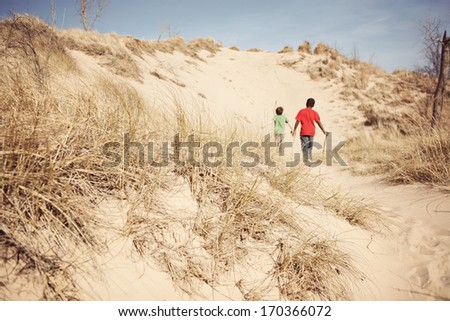Boys exploring a sand dune - stock photo