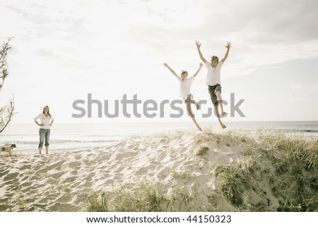 Boys jumping of a sand dune at the beach - stock photo