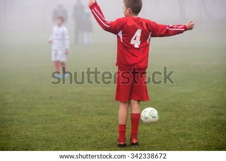 boys kicking football on the autumn - stock photo