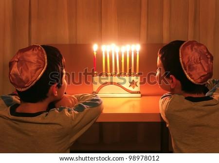 boys looking at hanukkah menorah - stock photo