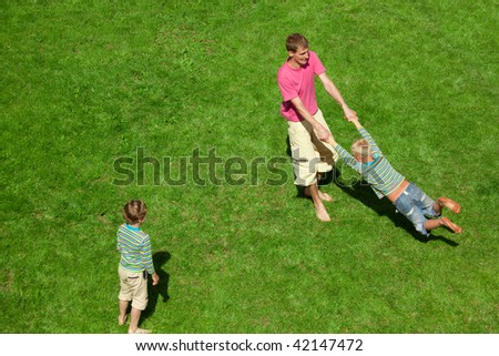 Boys play with the man outdoor. The Top view. - stock photo