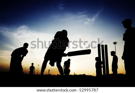 Boys playing cricket in the evening - stock photo