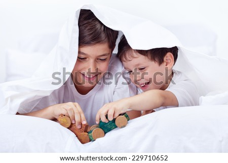 Boys playing in bed with wooden toys - brothers enjoying time together - stock photo