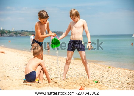 boys playing on the beach building sand castles on a sunny summer day - stock photo